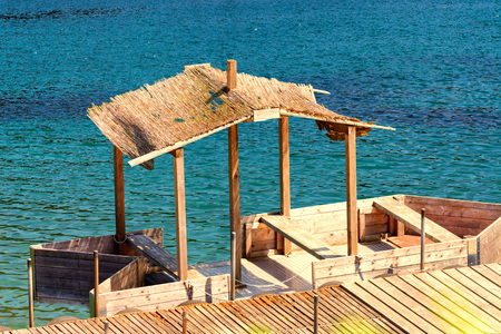 Boat bridge with simple boat house or wooden boat with thatched roof. Stock Photo