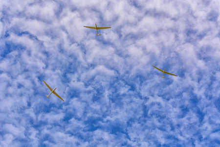 3 gliders in the blue sky. Motorless flying with a glider by using the thermal.