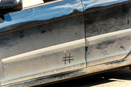 Side view of a filthy car. Concept hashtag #Wasch Me Car Wash