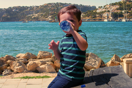 Thirsty little boy sitting on a wooden bench and drinking mineral water. In the background a Mediterranean port. 版權商用圖片