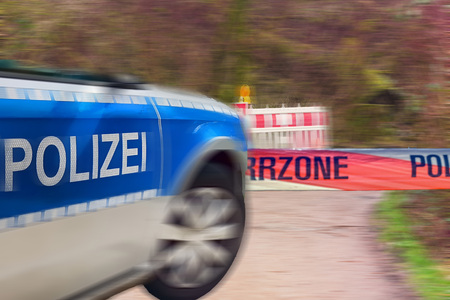 Intentional motion blur. German police car at the scene. Barrier that says