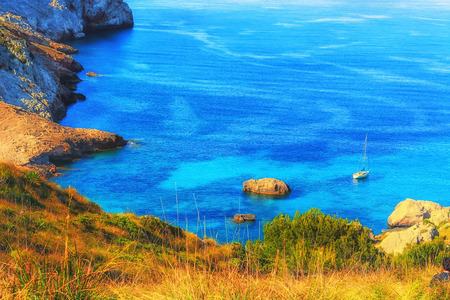 Picturesque sea landscape with bay and sailing ship on Mallorca, Baleares in Spain.