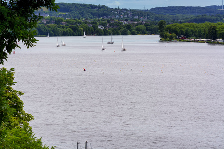 ESSEN, NRW, GERMANY - JUNE 10, 2017: Panoramic view from Baldeney Lake (Baldeneysee). In the background sailing boats at a sailing regatta.