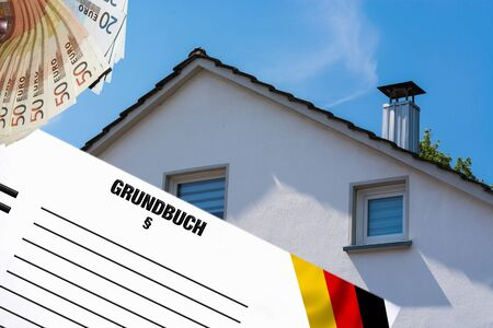 Gable side of a multi-family house of the 60s after the modernization against the blue sky. In the foreground white note with inscription in german land register. Foto de archivo