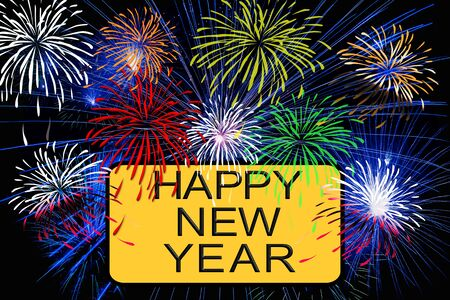 Happy new year text on yellow sign with fireworks in the night sky