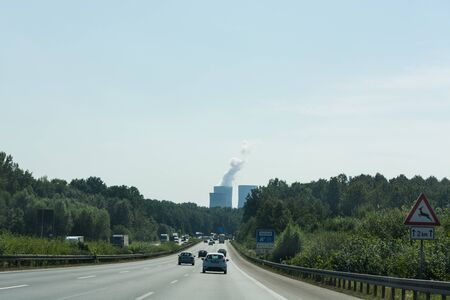 UNNA, GERMANY - AUGUST 23, 2017: Traffic on the A2 motorway and Scholven coal power station, Germany, North Rhine-Westphalia. Editorial