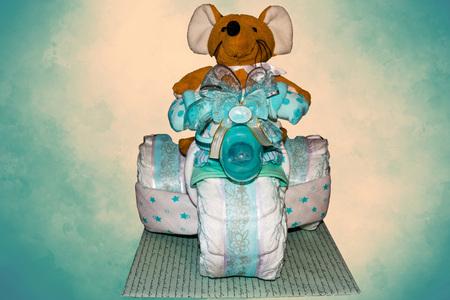Gâteau de couches Un gâteau de couches Tricycle avec des rubans bleus. Cadeau pour la naissance d'un enfant
