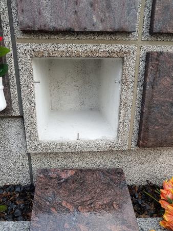 Un columbario de piedra con un nicho vacío y sin urna.