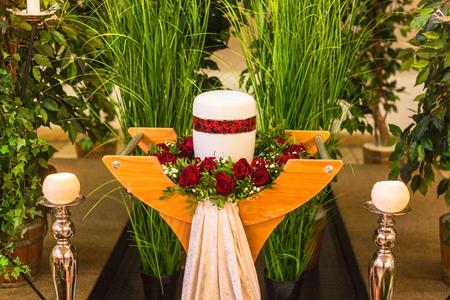 Concetto funerario e di lutto, urna rossa bianca del crematorio sul tavolo in chiesa