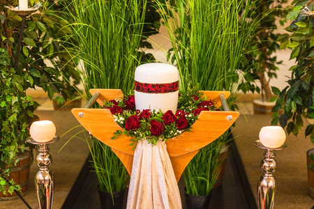 Funeral and mourning concept, crematorium white red urn on table in church