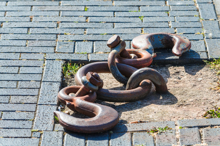 Old and rusty mooring ring for ships fixing. Dock for small boats.