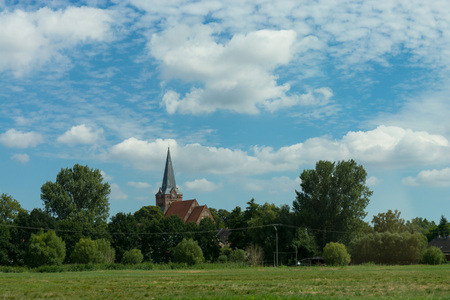 Countryside panorama blue sky Village church in the background Stock Photo