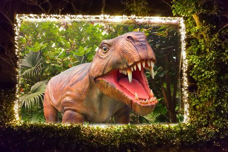 Billboard framed in a hedge with a string of lights on which a dinosaur is depicted. With clipping path