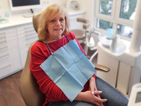 Portrait of a charming blonde lady with open eyes sitting in a dental chair and smiling Standard-Bild