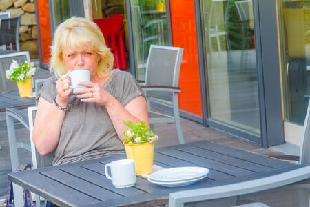 Blond woman enjoys a coffee in a sidewalk cafe. Stock fotó