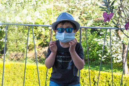 Little boy with a hat and sunglasses and respirator