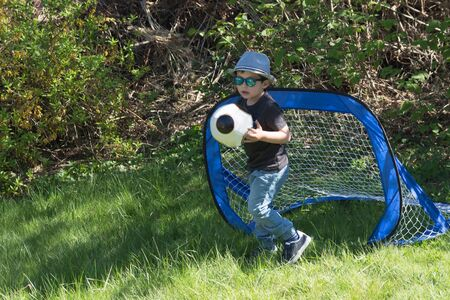 Little boy with hat and sunglasses while playing football in a garden Stock fotó