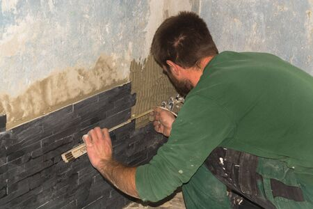 Workers install ceramic retro effect brick tiles