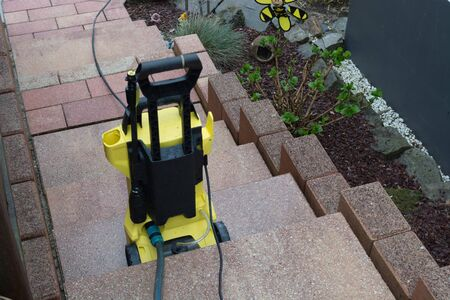 Yellow pressure washer on a staircase with hose and pistol Stock fotó