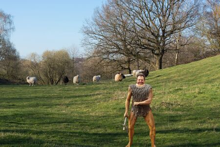 Cartoon illustration of a Neanderthal figure made of plastic with hatchet on a meadow while hunting for sheep Stock fotó