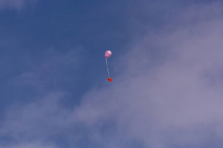 Pink balloon with ribbon and greeting card in front of blue sky Фото со стока