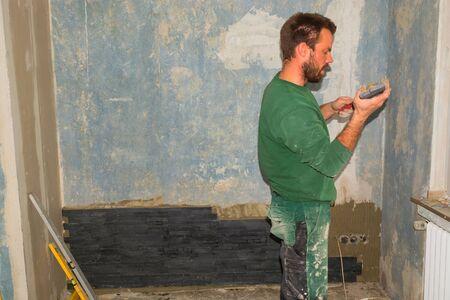 Workers install ceramic retro effect brick tiles