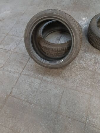 Two new tires are lying on the floor in the workshop