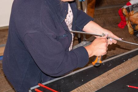 Woman in laying a laminate floor - closeup on female hands. Banque d'images