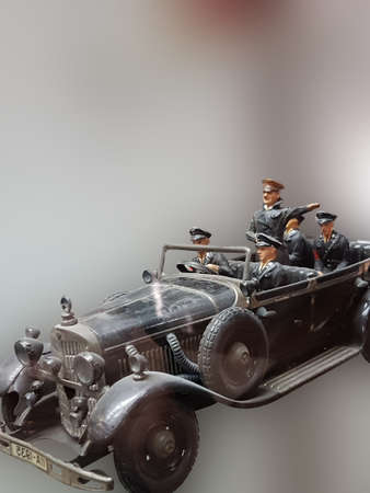 RATINGEN, NRW, GERMANY - AUGUST 17, 2018:Selective focus views of a model car made of sheet metal with tin soldiers on an exhibition.