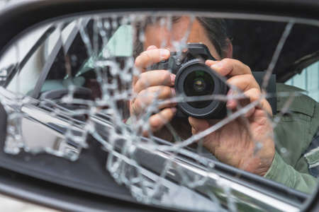 Reflection in side mirror Paparazzi man sitting inside the car and photographing with slr camera. Standard-Bild