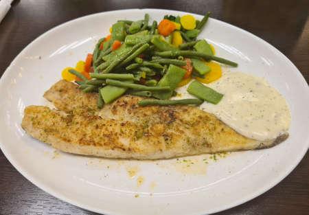 Fried fish on green asparagus with salad Standard-Bild