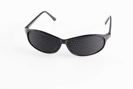 weary: Pinhole eyeglasses help relaxing weary eyes, on white background. Stock Photo