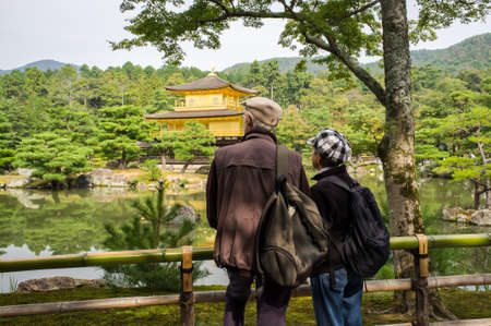 silently: Kyoto, Japan, October 17, 2011 - The visitors standing in front of the Kinkakuji temple silently admired the beauties and tranquilities of the golden pavilion.
