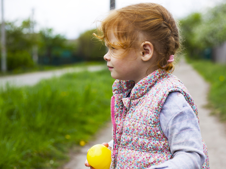little redhead girl with pigtails looks away close-up
