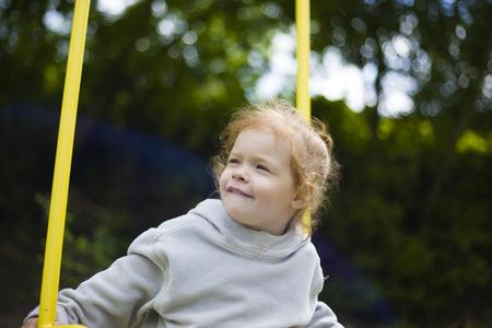 schönes süßes kleines rothaariges Mädchen, das auf einer Schaukel auf dem Spielplatz reitet
