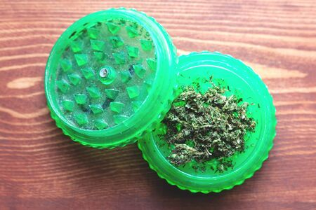 plastic grinder weed close-up chopping buds cannabis for smoking on the wooden background