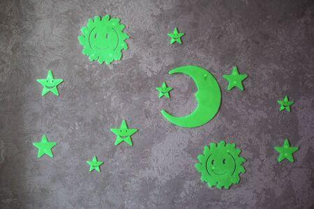 Leuchtende phosphorhaltige Sonne, Mond und Sterne auf grauer Hintergrundnahaufnahme