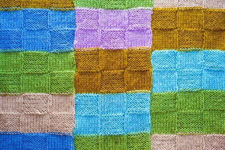 texture of multicolored fragments of knitted cover,background of colorful threads close-up