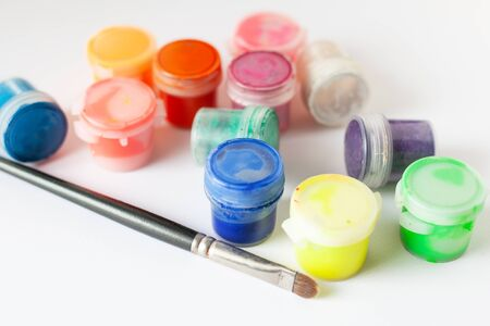 multi-colored tubes of gouache and paint brush on a white background close-up