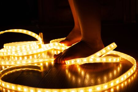 baby legs, little girl stepping on LED strip, naughty baby playing with electricity, child safety concept and parental control  close-up