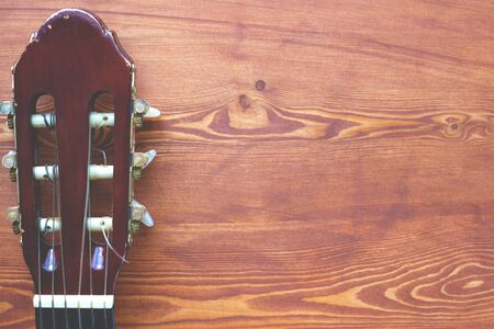 wooden background with a fingerboard from the guitar, music flatlay frame top view close-up