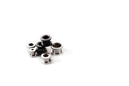 a set of ear tunnels of different sizes, black and chrome color on a white background. piercing close up Isolate