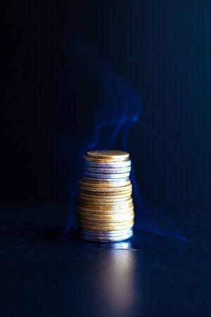 brûler des dollars et des euros en pièces. une pyramide financière brûlante de gros plan sur la capitalisation de l'argent