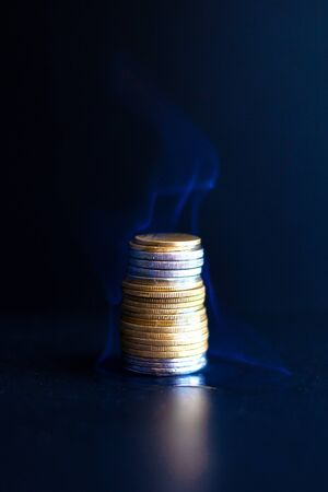 burning dollars and euros in coins. a burning financial pyramid of money capitalization close-up