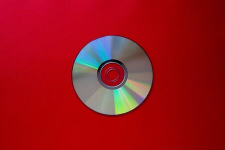 cd compact disc on a Dark red background top view with copy space close-up Фото со стока