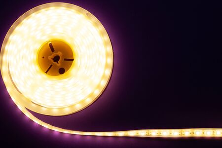 LED strip on a dark purple background, diode light copy space close-up