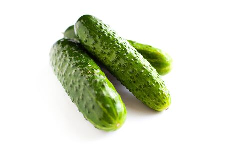small gherkins, delicious fresh cucumbers on a white background close-up