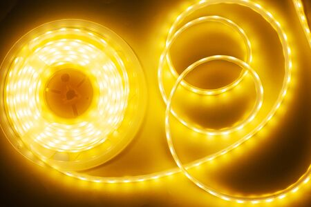 bright yellow LED strip, diode strip, a coil  of silicone strip close-up Imagens