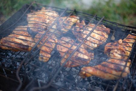charcoal chicken cooking process, grilled meat with smoke outdoors picnic  close-up