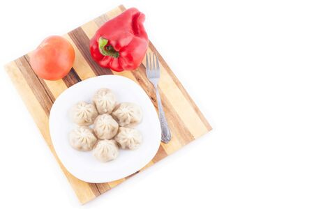 boiled dumplings with sauce and pepper in a plate on a wooden stand with vegetables, a traditional Russian dish  top view close-up